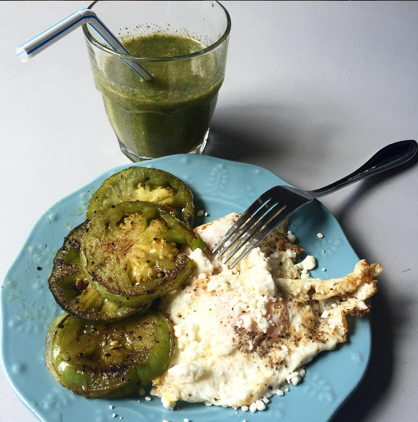 brunch of fried eggs with feta cheese, fried green tomatoes, and  a green smoothie